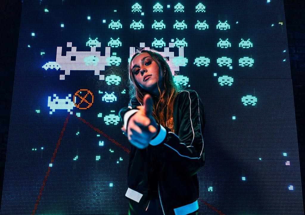 Une jeune joueuse pointant sa main façon pistolet avec les ennemis du jeu Space Invaders derrière elle