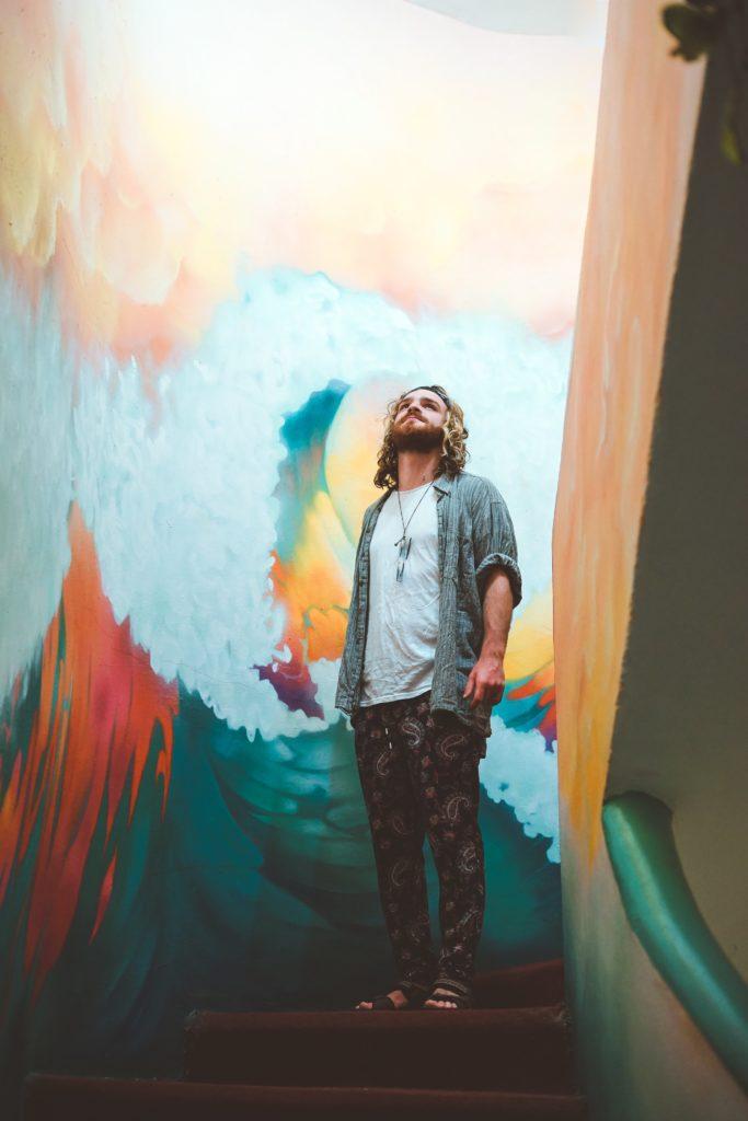 Jeune homme entouré de peintures