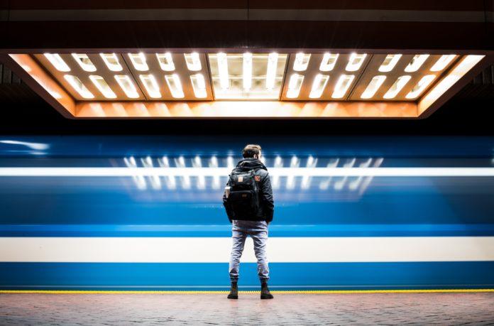 Jeune homme seul et portant un sac à dos sur fond bleu et orange