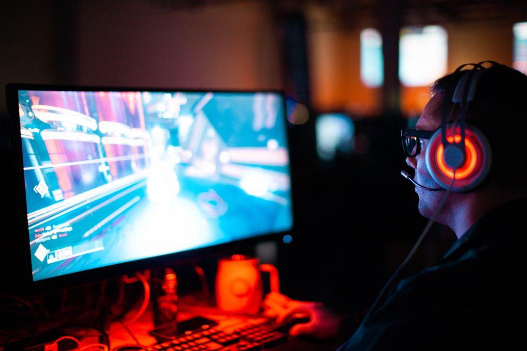 Une joueur avec un casque rouge devant son écran d'ordinateur