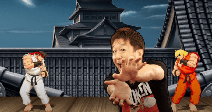 Yoshinori Ono de chez Capcom qui mime un hadoken avec les mains jointes devant une partie de street Fighter II