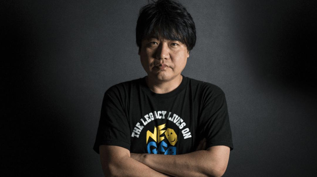 Le producteur de SNK Yasuyuki Oda croisant les bras et portant un t-shirt noir Neo Geo