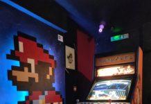 Borne d'arcade Street Fighter avec mario peint sur le mur d'à côté