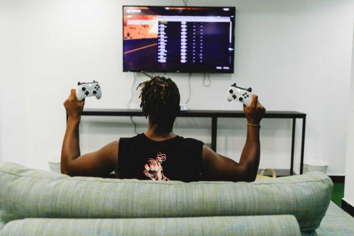 Un homme noir tenant deux manettes de Xbox devant la télé